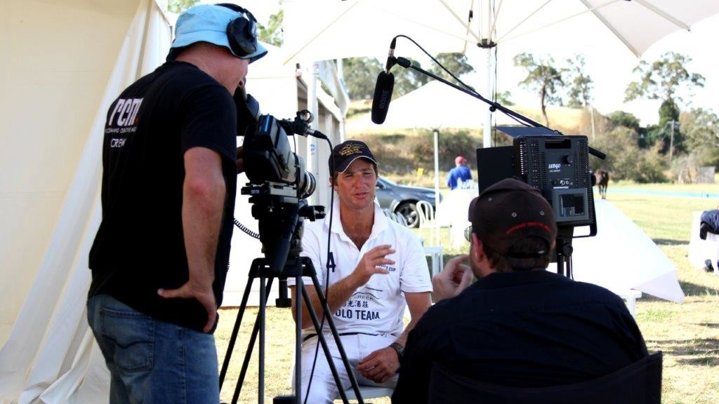Photo of Director and Cameraman interviewing a polo player