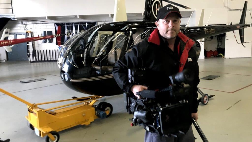 Video Director holding camera at helicopter hanger