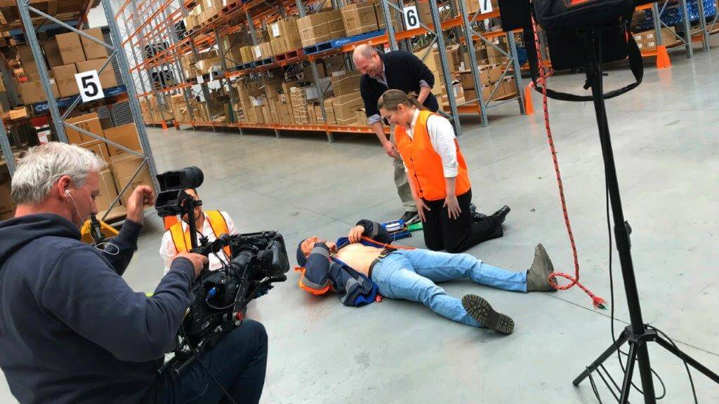 Camera operator with Director and Actors creating a training video for an AED device